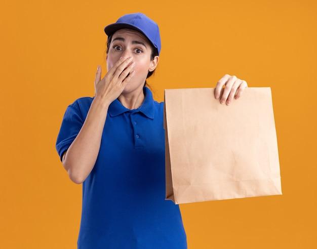 Preoccupata giovane donna delle consegne in uniforme e cappuccio che tiene un pacchetto di carta tenendo la mano sulla bocca