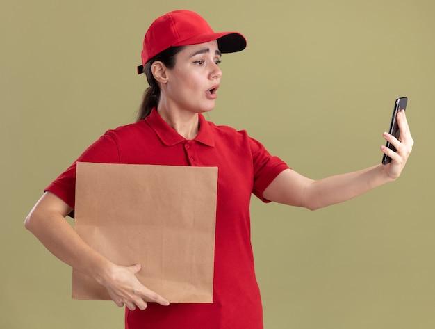 Giovane donna delle consegne preoccupata in uniforme e cappuccio che tiene in mano un pacchetto di carta e un telefono cellulare che guarda il telefono