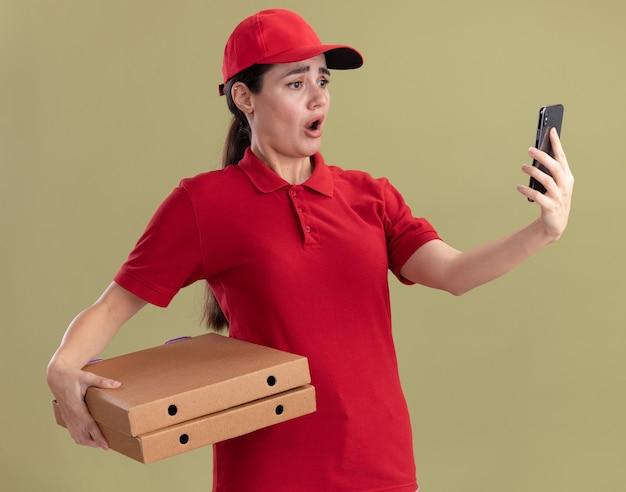 Giovane donna delle consegne preoccupata in uniforme e berretto che tiene in mano pacchi di pizza e telefono cellulare che guarda il telefono