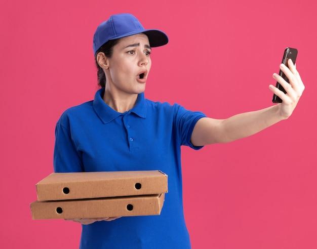 Preoccupata giovane donna delle consegne in uniforme e berretto che tiene in mano pacchetti di pizza che si fanno selfie