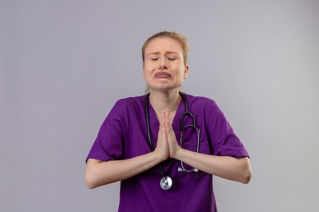 紫色の医療用ガウンと聴診器を身に着けている心配している若い医者は、孤立した白い壁に祈りのジェスチャーを示しています