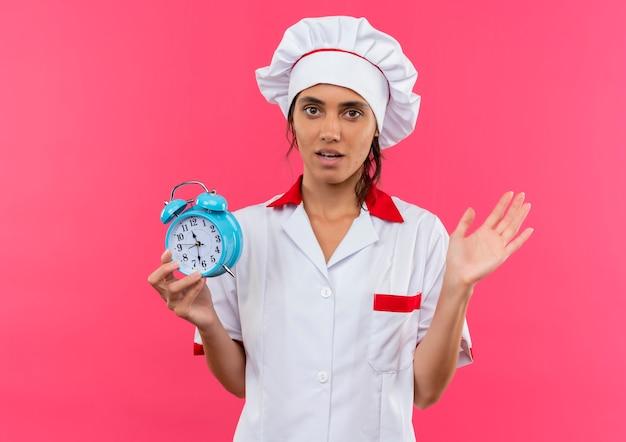 目覚まし時計を保持しているシェフの制服を着て心配している若い女性料理人は、コピースペースのある孤立したピンクの壁に手を広げた