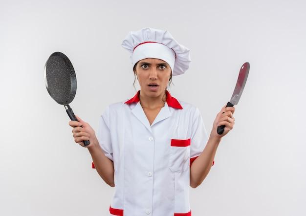 コピースペースのある孤立した白い壁に包丁とフライパンを保持しているシェフの制服を着ている心配している若い女性料理人