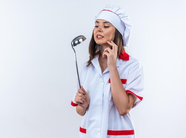 白い背景で隔離のお玉を保持しているシェフの制服を着て心配している若い女性料理