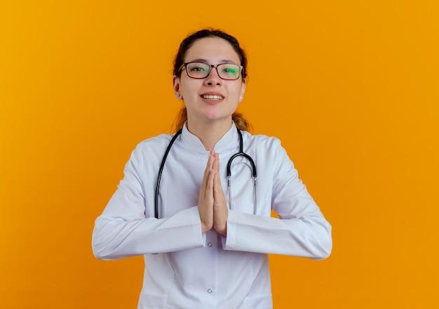 Preoccupato giovane medico femminile che indossa abito medico e stetoscopio con gli occhiali che mostrano pregare gesto isolato