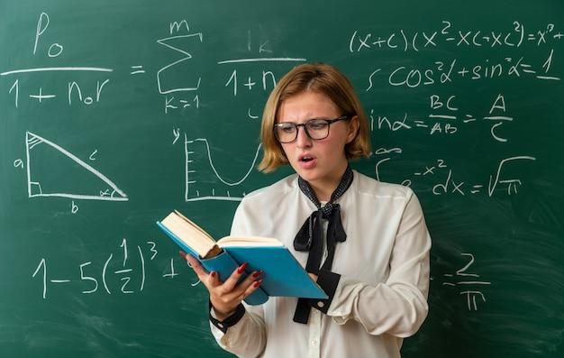 Обеспокоенная молодая учительница в очках, стоящая перед доской, читая книгу в классе