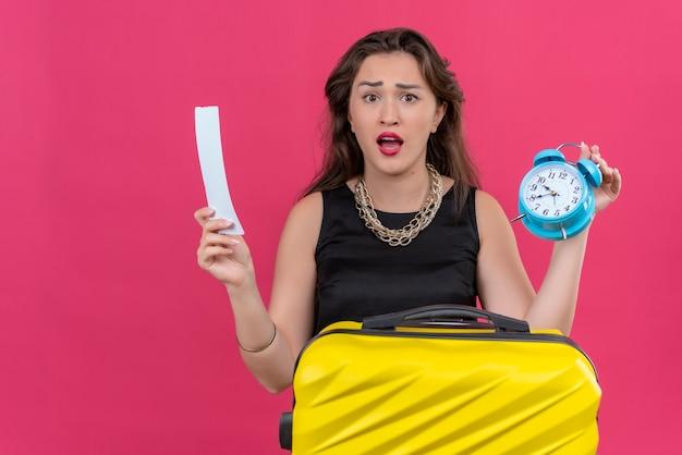 Обеспокоенная молодая женщина-путешественница в черной майке держит будильник и билет на красной стене