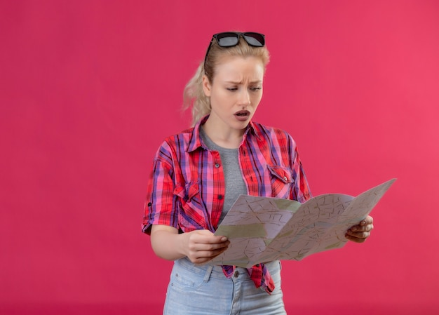 Concerned young female traveler wearing red shirt and glasses on her head looking to map on isolated pink wall