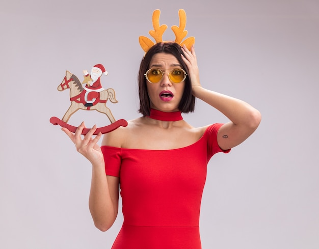 Concerned young girl wearing reindeer antlers headband and glasses holding santa on rocking horse figurine keeping hand on head looking at camera isolated on white background