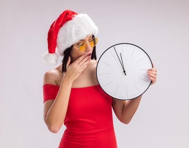 サンタの帽子と眼鏡をかけて、白い背景で隔離の口に手を保持し、時計を見て心配している若い女の子
