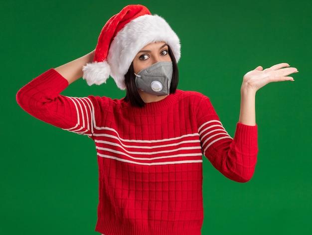 サンタの帽子と保護マスクを身に着けている心配している若い女の子が緑の背景で隔離の空の手を示す頭に手を置いてカメラを見て