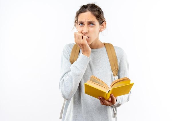 Un giovane studente preoccupato che indossa uno zaino con in mano un libro morde le unghie