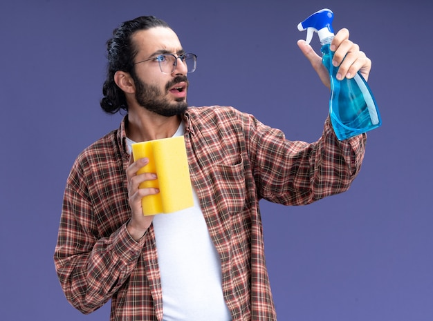 Concerned young handsome cleaning guy wearing t-shirt holding sponge looking at spray bottle in his hand isolated on blue wall
