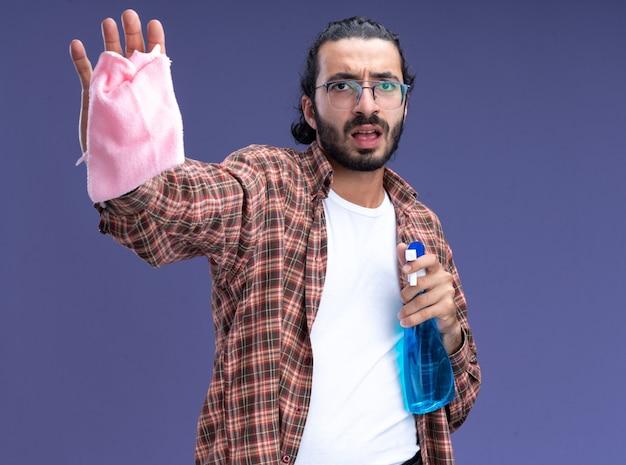 青い壁に分離された停止ジェスチャーを示すぼろきれとスプレーボトルを保持しているtシャツを着ている心配している若いハンサムな掃除人