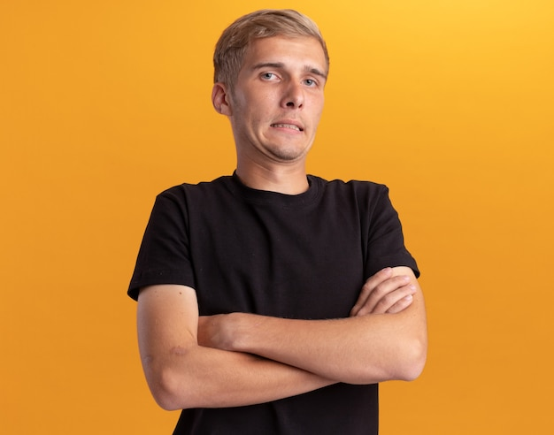 Concerned young handsome guy wearing black shirt crossing hands isolated on yellow wall
