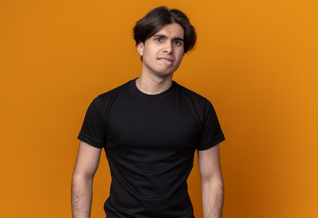 Concerned young handsome guy wearing black t-shirt bites lips isolated on orange wall