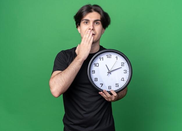 Preoccupato giovane bel ragazzo che indossa la maglietta nera che tiene l'orologio da parete coperto la bocca con la mano isolata sulla parete verde con lo spazio della copia