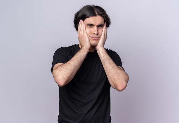 Обеспокоенный молодой красивый парень в черной футболке, положив руки на щеки, изолированные на белой стене