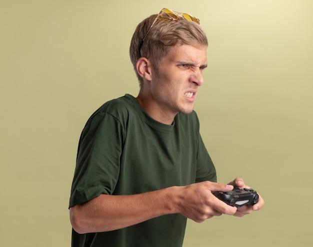 Обеспокоенный молодой красивый парень в зеленой рубашке с очками на голове играет в игру на джойстике игрового контроллера, изолированном на оливково-зеленой стене