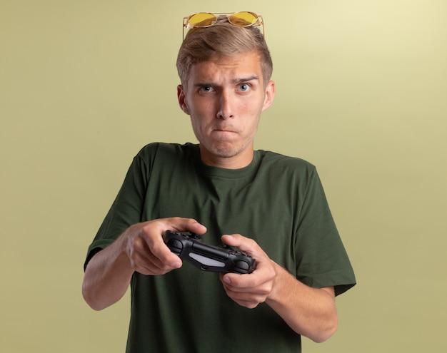Обеспокоенный молодой красивый парень в зеленой рубашке с очками на голове играет на джойстике игрового контроллера, изолированном на оливково-зеленой стене
