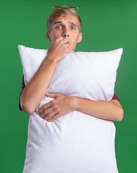 Il giovane ragazzo bello interessato che porta il cuscino abbracciato camicia rossa morde i chiodi isolati sulla parete verde