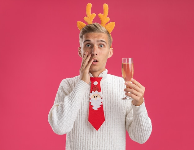 Concerned young handsome guy wearing reindeer antlers headband and santa claus tie holding glass of champagne looking at camera touching face isolated on pink background