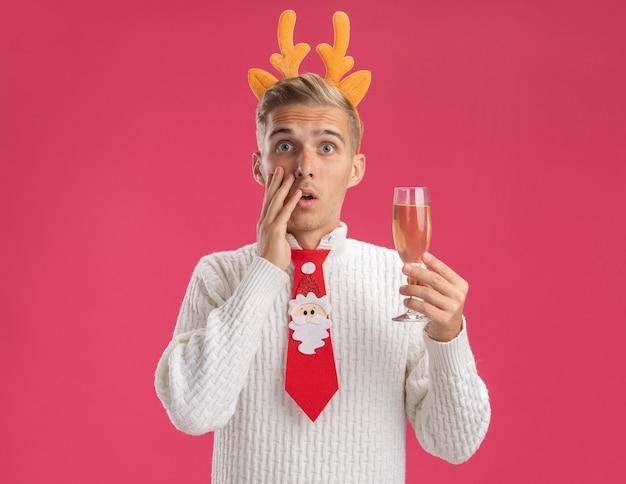 Preoccupato giovane bel ragazzo che indossa la fascia di corna di renna e cravatta di babbo natale che tiene un bicchiere di champagne toccando il viso isolato sul muro rosa con spazio di copia