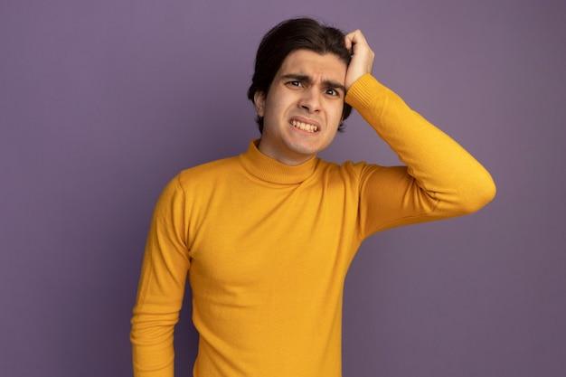 紫色の壁に隔離された寺院に手を置く黄色のタートルネックのセーターを着ている心配している若いハンサムな男