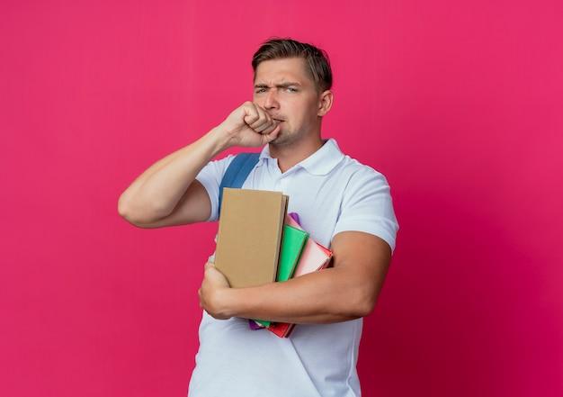 Обеспокоенный молодой красивый студент-мужчина держит книги и кладет кулак на подбородок на розовой стене
