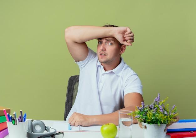 올리브 그린에 고립 된 이마에 팔을 넣어 학교 도구로 책상에 앉아 우려 젊은 잘 생긴 남자 학생