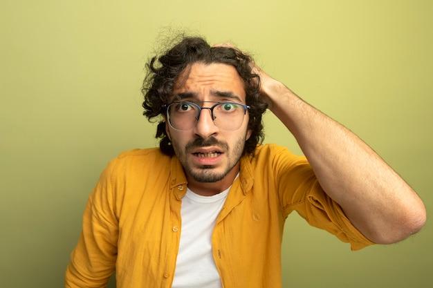 心配している若いハンサムな男は、オリーブグリーンの壁に隔離された頭に手を置いて正面を見て眼鏡をかけています