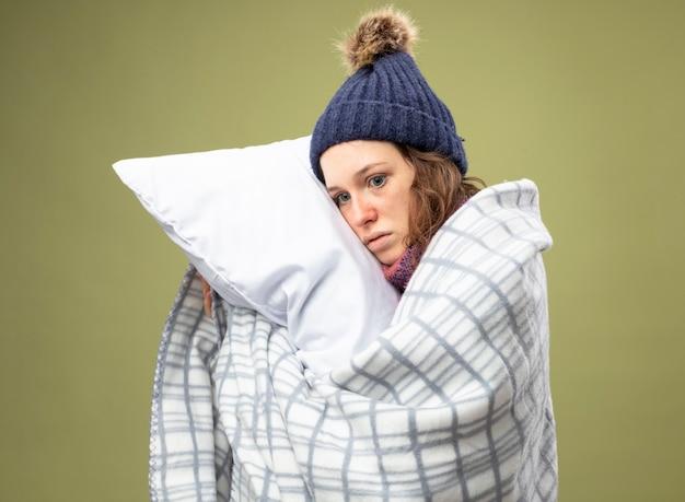 格子縞に包まれたスカーフと白いローブと冬の帽子を身に着けている側を見て心配している若い病気の女の子