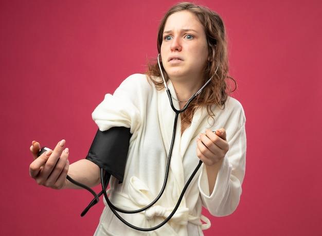Обеспокоенная молодая больная девушка в белом халате, смотрящая в сторону, измеряет собственное давление с помощью сфигмоманометра, изолированного на розовом