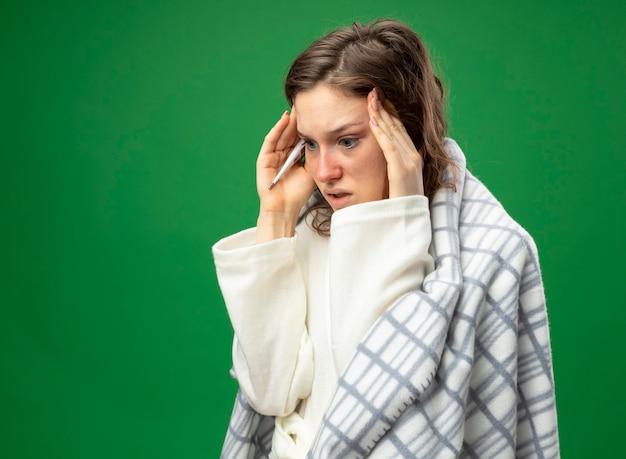 コピースペースで緑に隔離された寺院に手を置く格子縞に包まれた白いローブを着て横を見て心配している若い病気の女の子