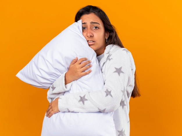 Concerned young ill girl looking at camera hugging pillow isolated on yellow background