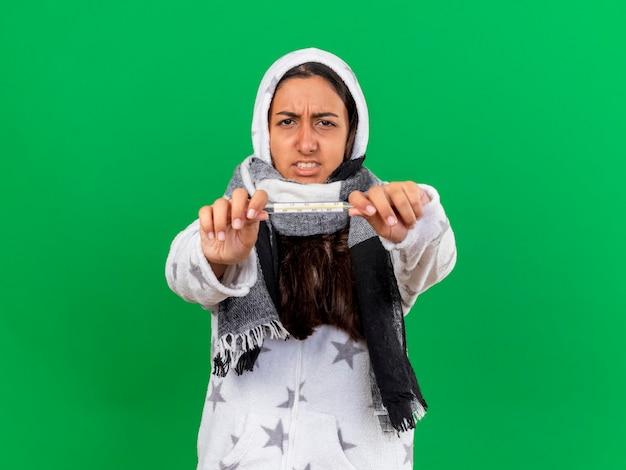 緑の背景に分離されたカメラで温度計を差し出しているフードwearinスカーフを身に着けている心配している若い病気の女の子