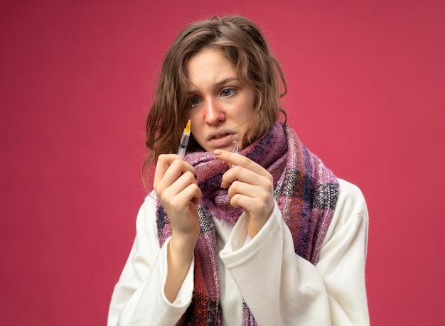 Обеспокоенная молодая больная девушка в белом халате и шарфе держит и смотрит на шприц с ампулой, изолированной на розовом