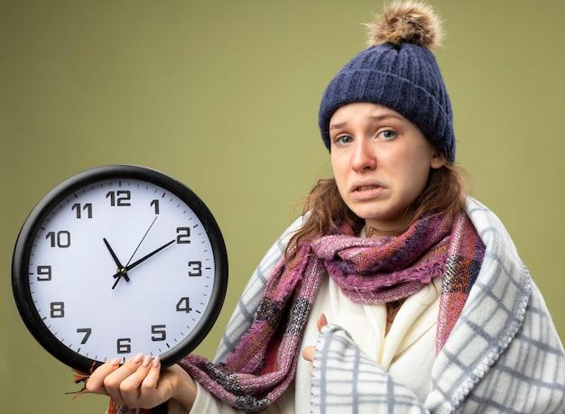 Обеспокоенная молодая больная девушка в белом халате и зимней шапке с шарфом держит настенные часы, завернутые в плед, изолированные на оливково-зеленом