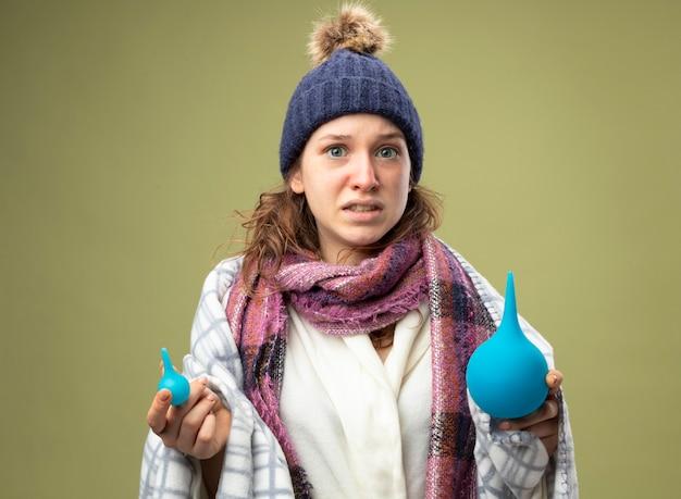 オリーブグリーンで隔離された浣腸を保持している格子縞に包まれたスカーフと白いローブと冬の帽子を身に着けている心配している若い病気の女の子