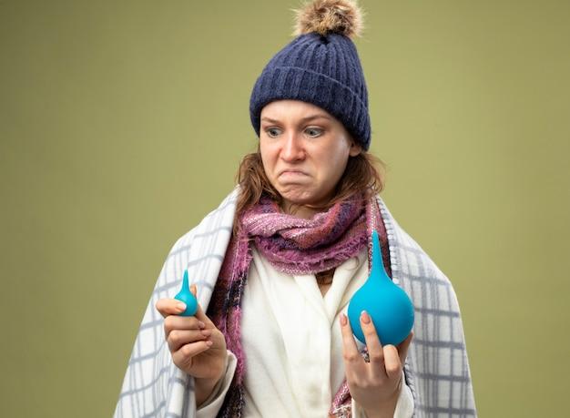 Preoccupato per la giovane ragazza malata che indossa una veste bianca e cappello invernale con sciarpa avvolta in un plaid che tiene e guardando i clisteri isolati su verde oliva
