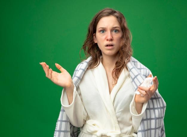 Обеспокоенная молодая больная девушка в белом халате, завернутом в плед, держит салфетку, разводя руками, изолированными на зеленом с копией пространства