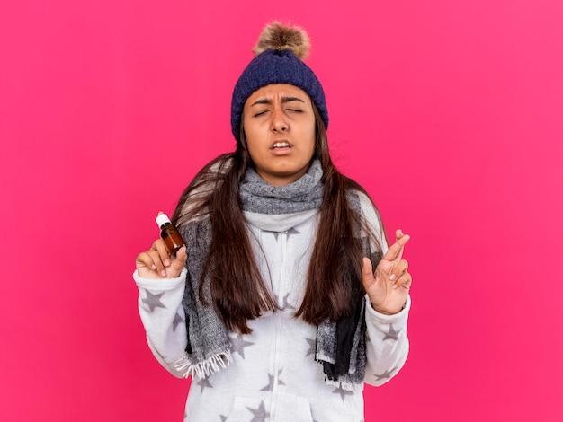 Обеспокоенная молодая больная девушка с закрытыми глазами в зимней шапке с шарфом держит лекарство в стеклянной бутылке, скрещивая пальцы, изолированные на розовом
