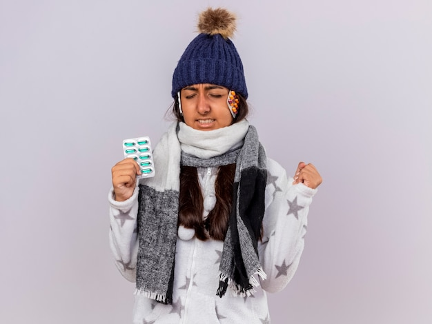 Concerned young ill girl with closed eyes wearing winter hat with scarf holding pills putting pills under hat and showing yes gesture isolated on white background