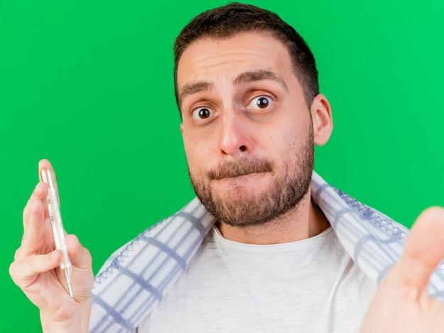 Обеспокоенный молодой больной мужчина держит термометр с камерой, завернутый в плед, изолированный на зеленом