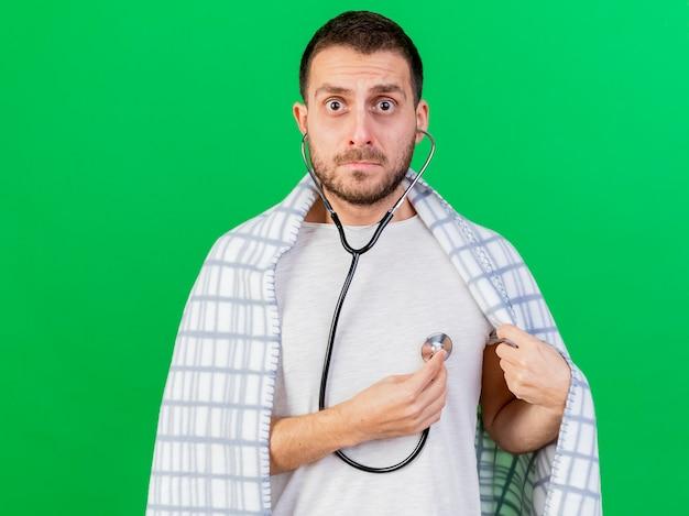 Preoccupato giovane uomo malato che indossa e ascolta il proprio battito cardiaco con lo stetoscopio isolato su sfondo verde