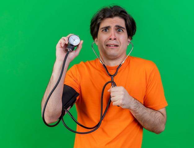 Stetoscopio da portare preoccupato del giovane uomo malato che tiene lo sfigmomanometro isolato sul verde