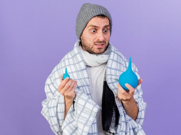 Preoccupato giovane uomo malato che indossa cappello invernale con sciarpa che tiene e guardando clistere isolato su sfondo viola