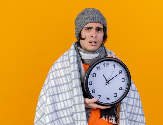 Preoccupato giovane uomo malato che indossa un cappello invernale con sciarpa avvolta in un plaid tenendo l'orologio da parete isolato su arancione