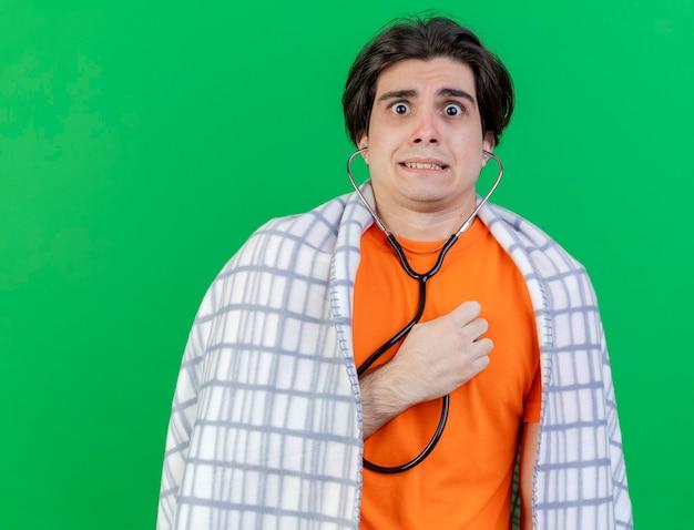 Preoccupato giovane uomo malato avvolto in un plaid che indossa e ascolta il proprio battito cardiaco con lo stetoscopio isolato su sfondo verde