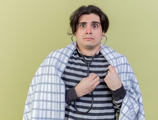 Preoccupato giovane uomo malato avvolto in un plaid che indossa e ascolta il proprio battito cardiaco con uno stetoscopio isolato su sfondo verde oliva